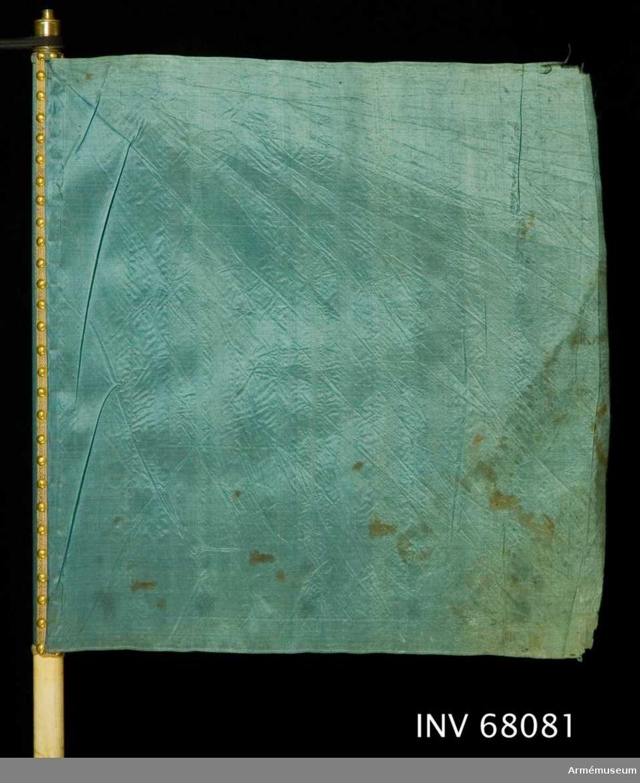 Duk: Tillverkad av blå sidentaft. Duken fäst med en rad tennlickor på mönstervävt band.  Dekor: Saknas  Stång: Tillverkad av trä, vitmålad. Holk av mässing. Spets saknas.  Skinnremmar: En övre, vit skinnrem genomstucken i stången 700-720 mm längd från dukens fäste mätt, bildar en 300 mm lång ögla.   Den nedre remmen brun, del saknas. Nuvarande längd 560 mm, fäst rakt igenom stången 55 mm respektive 70 mm mätt nedifrån.