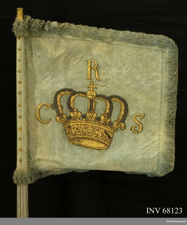 Duk: Tillverkad  av enkel blå sidendamast, sammansydd av två delar. Mönster i form av spridda blomkvistar. Duken fäst med tre rader tennlickor på ett mönstervävt band i blått.  Dekor: Målad lika på båda sidor, stor sluten krona i guld med silverpärlor på kronbyglarna samt bostäver i guld på sidorna och över kronan. Allt med konturer i brunt.  Frans: Dubbel, kraftig frans av blått silke.  Stång: Tillverkad av trä, kannelerad, gråmålad (i senare tid). Löpande bärring. Holk av förgylldmässing.