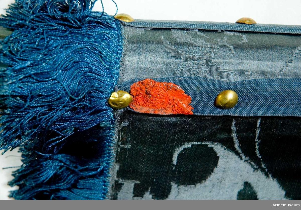 Duk: Tillverkad av enkel blå sidendamast. Mönsterrapport, höjden omätbar. Fäst med tre rader mässingsspikar på ett blått enkelt band. Längst ned på detta band ett rött sigill från Krigs Collegii.  Mönster: Dukens damast har en bisarr design.  Dekor: Målad lika på båda sidor, i övre inre hörnet tre eldsprutande berg (målade över en korsglob) i blåskuggat silver med lågor i rött och guld, Västmanlands vapen.  Frans: Enkel, tillverkad av blå silkesfrans.  Stång: Tillverkad av trä, kannelerad, grepp, blåmålad, avsågad. Holk och spets av förgylld mässing.  Banderoller av blått silke, bestående av en snodd och två tofsar.