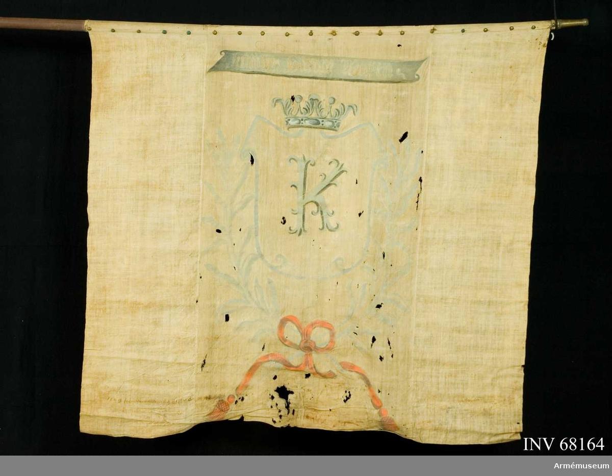 Duk: Tillverkad av enkel blå och gul linnelärft. Blå med gul bjälke. Sammansydd av tre våder. Duken fäst upptill, fäst med mässingstennlickor på vitt kypertvävt linneband.  Dekor: Målad omvänt lika i bjälkens riktning, med gråblå konturer en krönt sköld vari ett sirat K i grått och svart. Under skölden två korsade lagerkvistar i grått, hopbundna med rosett i rött. Över skölden ett inskriptionsband i gråblått med text i ljus färg, på dukens båda sidor.  Stång: Tillverkad av trä, avsågad. Holk av mässing.