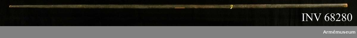 Fanstång, rundstav av furu, målad i svart och rött. Mitt på stången en mässingsögla.  Fragment av fastnitad fanduk: 1210 mm.