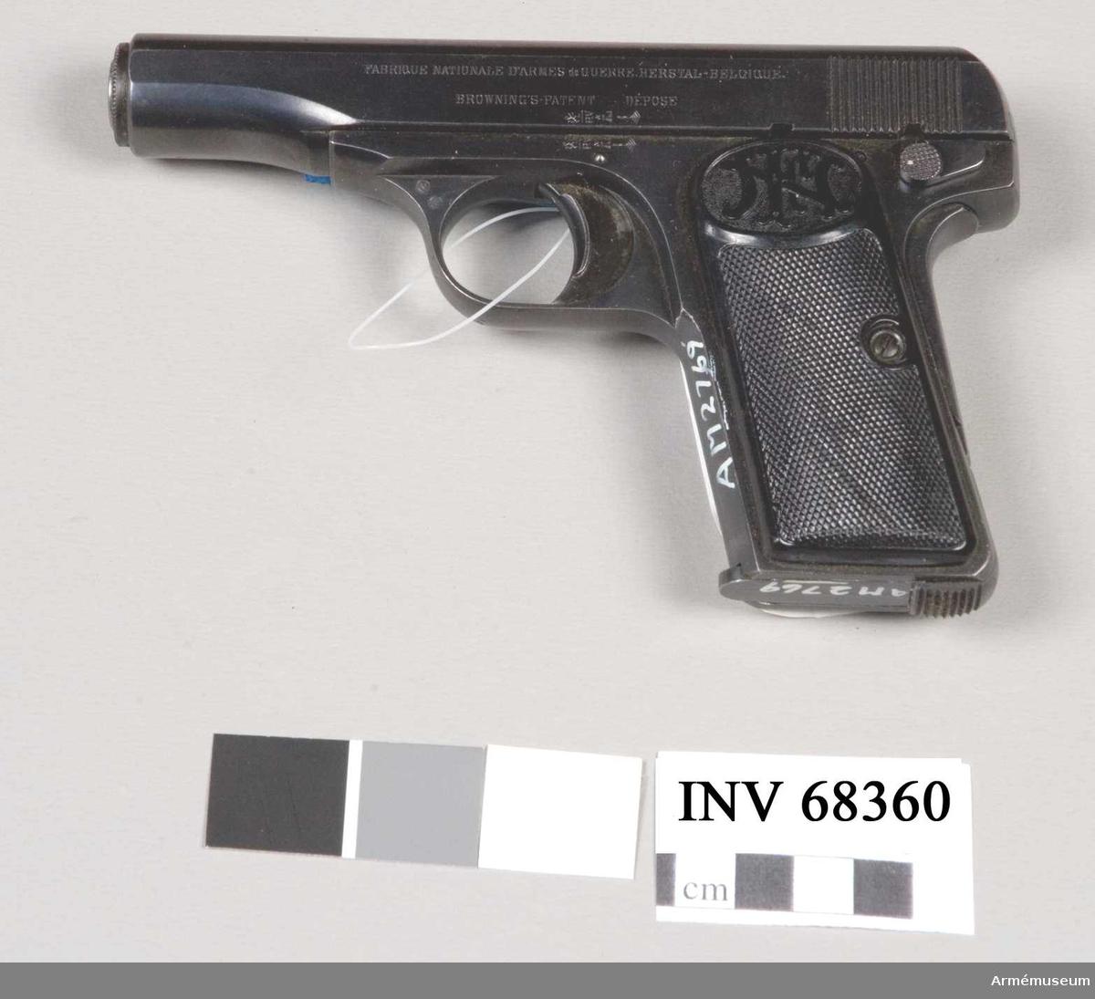"""Halvautomatisk pistol av system Browning. Består av: 1 pistol, halvautomatisk, 2 magasin, 1 läskstång, 1 laddblindpatron. Vapnet märkt """"(FN) P.V ÅL  (V) (R)""""."""