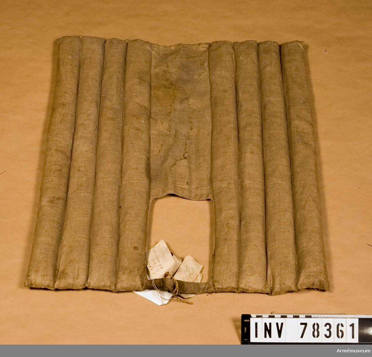 """Grupp: K I.  Tillverkad år: 1891. Plats: Paris. Betslet utgöres av stångbett och bridongbett med tyglar. Stångbetslet består av: huvudlag, stångbett och stångtyglar. Huvudlaget består av: a/ nackstycke, med 30 mm bredd i mitten och en knapp av mässing. Försedd med följande stämplar: """"Société Générale  de manufactures Militaires Paris"""" och """"Commission 17 11 91 Paris"""" b/ sidstycken, 22 mm breda, varje med två söljor av mässing 45 x 35 mm. , en halvrund ring av mässing och stämpel: """"Commission 12 12 91 Paris"""". c/ pannrem, 25 mm bred, rörlig, med två avlånga 35 x 25 mm:s bucklor av mässing och stämpel: """"Commission 16 11 91 Paris"""". Stångbettet består av: a/ mellanstycke, 20 mm i diam, med 12,5 cm bredd mellan sidstängerna. b/ sidstänger, 18,5 cm långa, med ovala öglor mellan mellanstycke och tygelringar. c/ vridbara tygelringar, 35 mm i diam. samt e/ lös kindkedja. Stångtyglarna äro 2,5 cm långa och 22 mm breda med söljor av mässing 45 x 35 mm. och stämplar: """"Commission 17 11 91 Paris"""". Hopspända i tygelringarna och hopsydda med varandra. Bridongbettet består av: a/ tredelat bett med 15,5 cm bredd mellan tygelringarna. b/ tygelringar, 45 mm i diam. c/ kedjor, 6,5 cm långa samt d/ försticklar, 7,5 cm långa. Bridongtyglarna äro lika med stångtyglarna och med stämplar: """"Commission 18 11 91 Paris""""."""