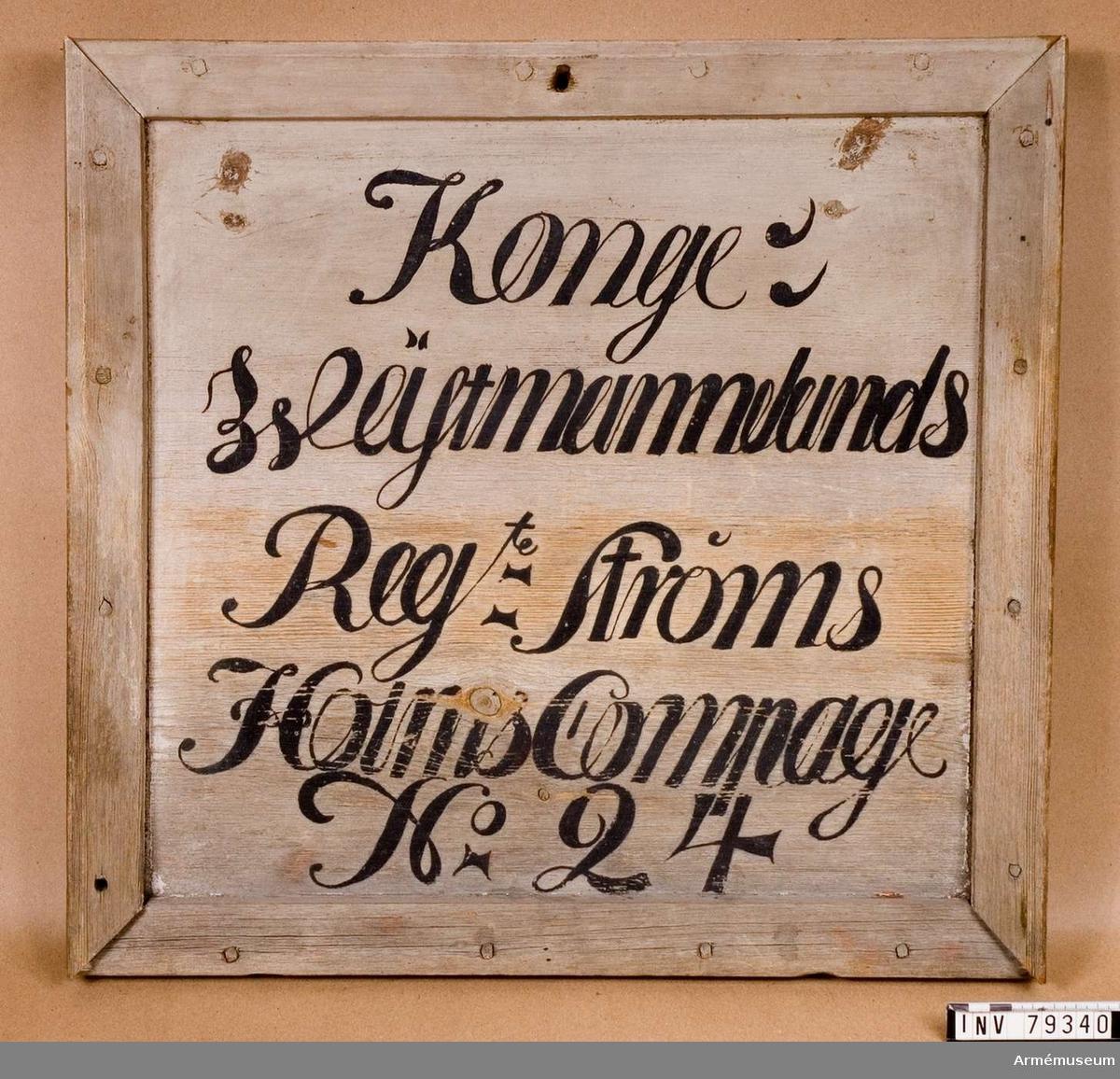 Grupp L. En ursprungligen vitmålad naturfärgad rektangulär trätavla med enkel, snidad ram. På tavlan läses i svart bokstäver: Kongl: Wästmanlands Reg-te Strömsholms Compagl No 24, på 5 rader.