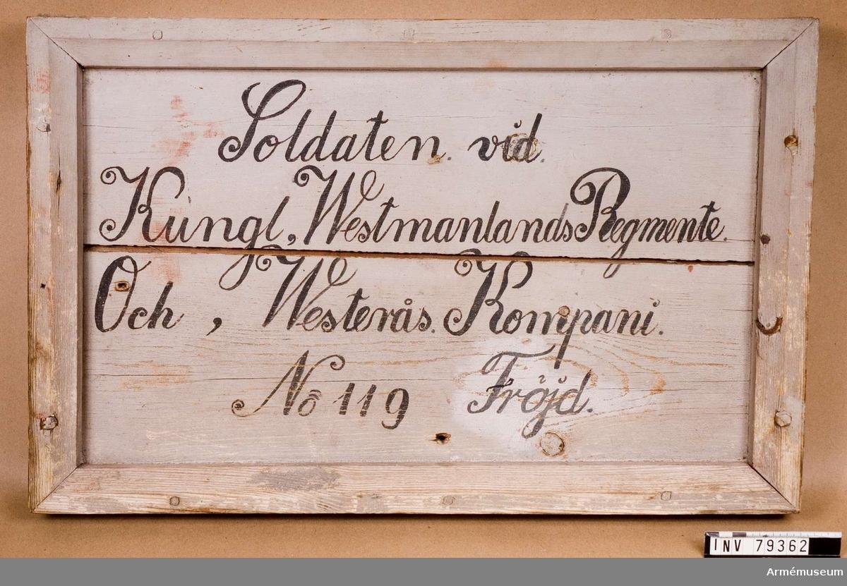 """Grupp L. Vitmålad med svart text:""""Soldaten vid Kungl.Westmanlands Regemente Och,(5) Westrås Kompani No 119 Fröjd"""" RÅBY ROTE  Tavlan ommålad vid namnet 1872, då Lejon fick sitt namn ändrat till Fröjd. 1847 Antogs Gustaf Wilhelm Leijon förut kallad Jansson född 1824. 1865 avskedas Gustaf Wilhelm Leijon på grund av sjuklighet. Roten ersatt med Johan Leijon förut kallad Jansson född 1845. 1872 begär Johan Leijon förut kallad Jansson """"att få ändra namn till Fröjd"""" vilket beviljas. 1878 Skarpskytten Johan Fröjd avskedas ad intimer den 18 januari 1878. Roten vacant. 1878 Carl Johan Fröjd förut kallad Magnusson född 1859 antagen den 29 november 1878. 1885 vice korporalen Carl Johan Fröjd förut kallad Magnusson."""