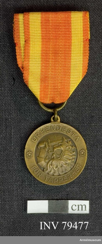 Grupp M.  Åtsidan: ¤ URHEUDESTA ¤ FÖR TAPPERHET.Överdelen av ett krönt (synnerligen heraldiskt) lejon åt vänster höjer med sitt bepansrade högra framben ett svärd.   Frånsidan: Inom en bandomvirad lagerkrans läses:SUOMEN KANSALTA 1918 på tre rader./Beskrivning: Carl Peyron.