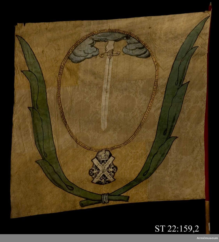 Duk av elfensbenfärgad kinesisk sidendamast. Ur ett moln en hand hållandes ett nedåtgående svärd. Runtom den ryska St Andreas orden i målad guldkedja. Allt inramas av palmblad i smaragdgrön sidendamast. Strumpa av rött kläde. Avkortad stång. Spetsen saknas.