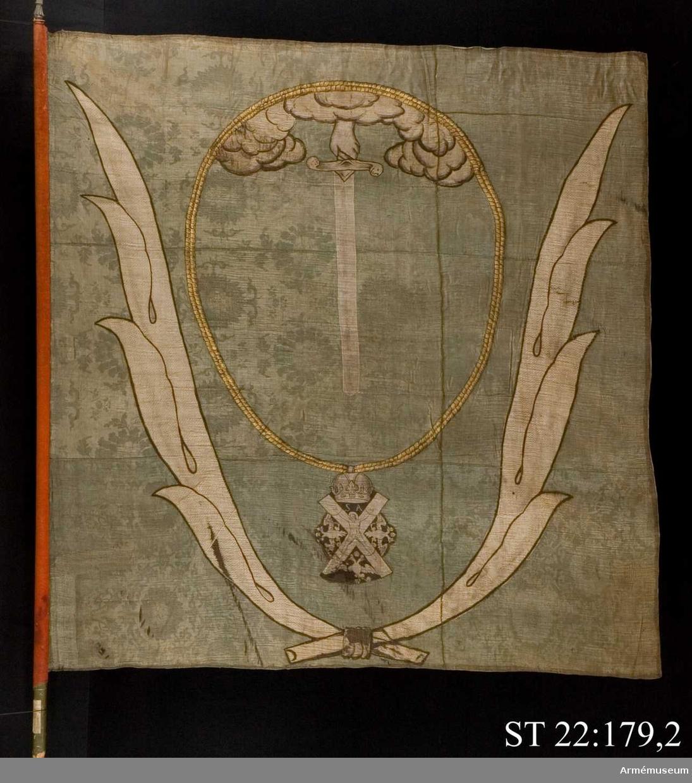 Duk av grön kinesisk sidendamast. Ur ett moln en hand hållandes ett nedåtgående svärd. Runtom den ryska St Andreas orden i målad guldkedja. Allt inramas av palmblad i vit sidenbaiberek. Grönmålad stång med bevarad spets.