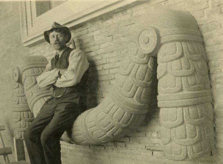 Bildhuggare Reinhold Pettersson sittande på en girlang gjord av huggen granit