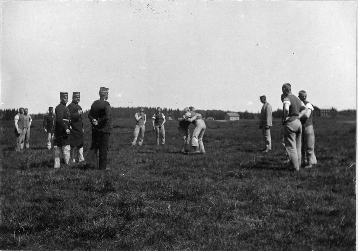 Soldater ur Älvsborgs regemente I 15 övar brottning på på Fristads hed. Officerare i uniform ser på vid sidan om.