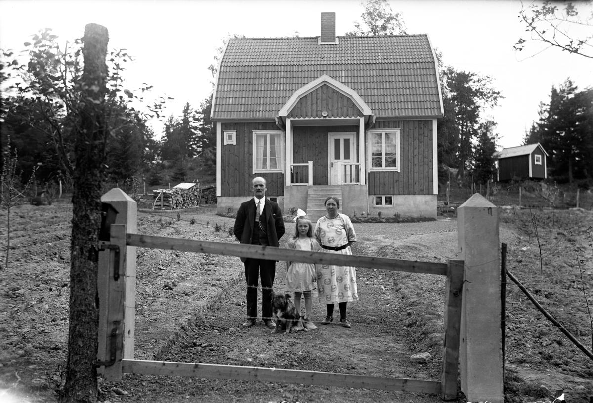 En man, en kvinna, en flicka och en hund i trädgården vid ett hus.