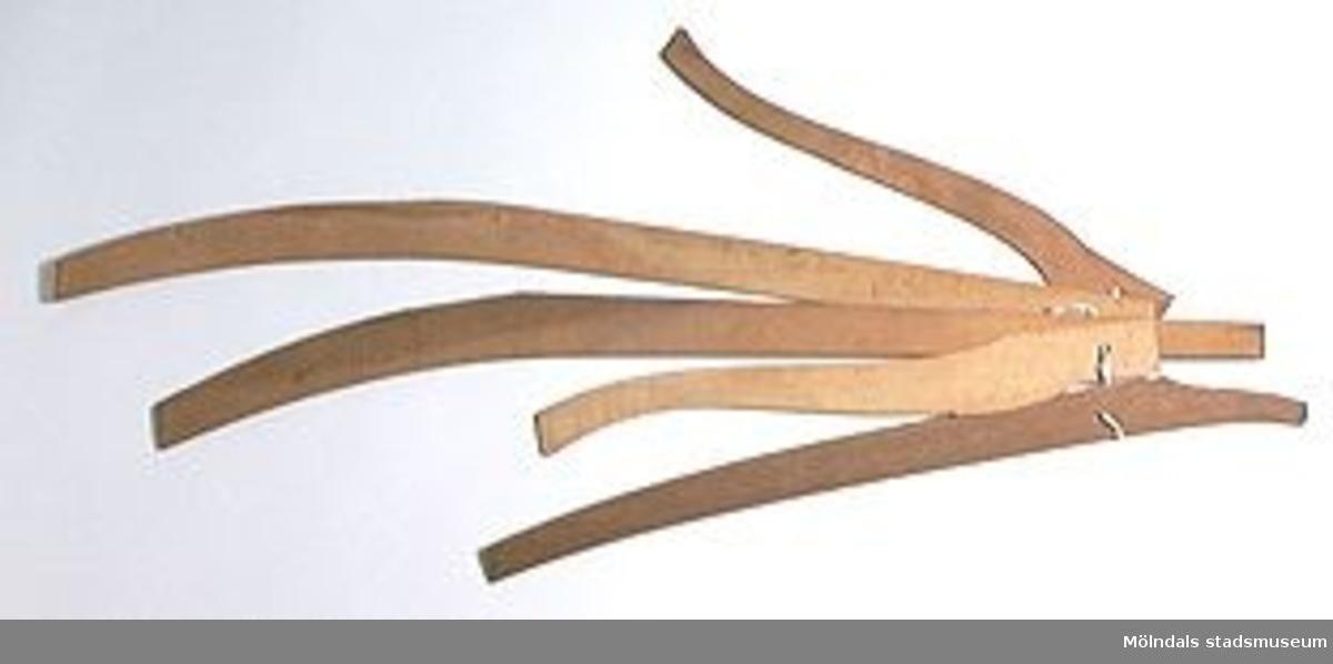 Möbelmall av trä, förmodligen detalj till stol. En av fem mallar (med Mölndals museums föremålsnummer 00213-00217), ihopsatta med snöre. Dock ej säkert att alla hör ihop.Litteratur: Red. Särnstedt Bo, Lindome Västsvenskt möbelsnickeri under 300 år, Stockholm 1977. Utställningskatalog från Liljevalchs Konsthall 1977-06-30-1977-09-11. Se sid 22-23 för historik kring fam. Thorsson.Mölndals Museum Lindomemöbler, Länstryckeriet Göteborg 1994. Utställningskatalog innehållande kapitel rörande familjen Thorssons verksamhet.