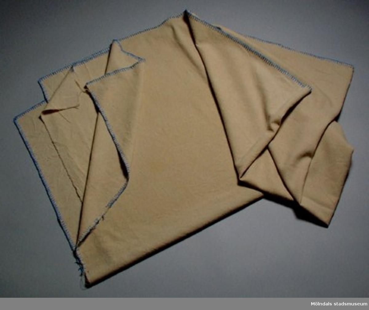 Beige maskinfilt kantad med blått garn. Använd i Papyrus papperstillverkning med användes av mölndalsbor som sängfilt. Material bomull?