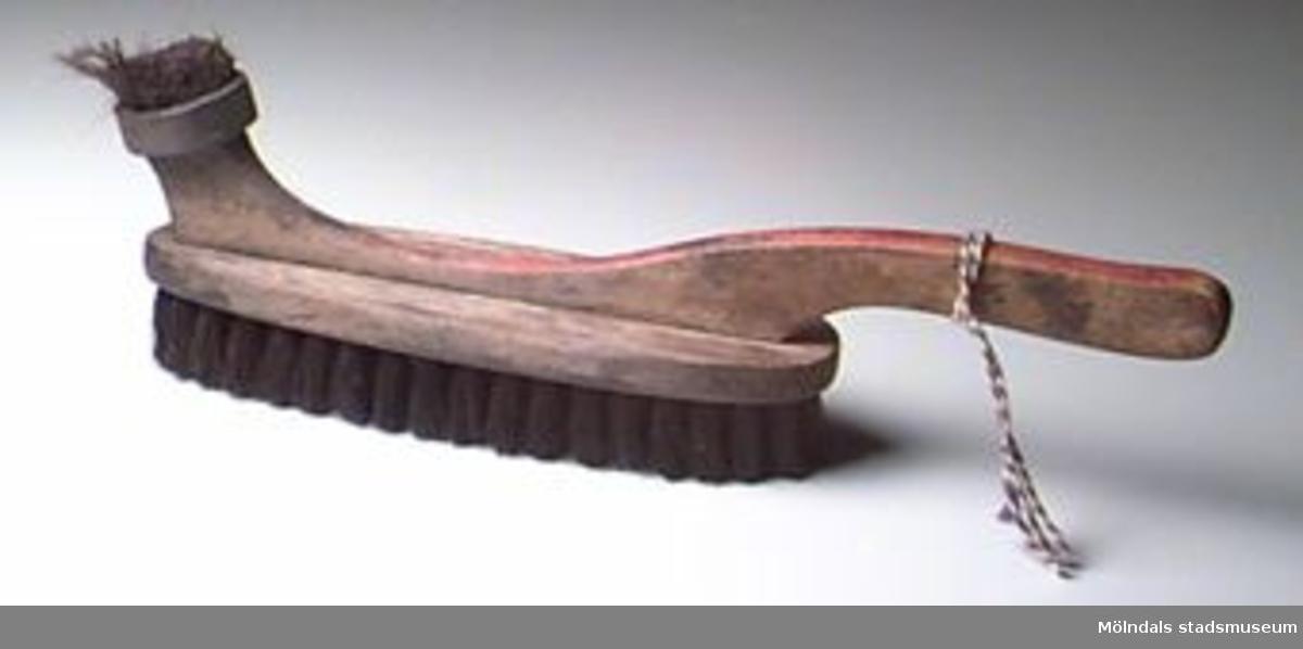 Oval borste med skaft och svarta borst. På ovansidan finns en liten rund borste att stryka på skokräm med. Rester av skokräm kvar på borsten. Skaftet rödmålat på över- och undersida. Träet mycket fläckigt. Blå-vitt snöre knutet runt skaftet.Ägaren var morfar till givarens fru.