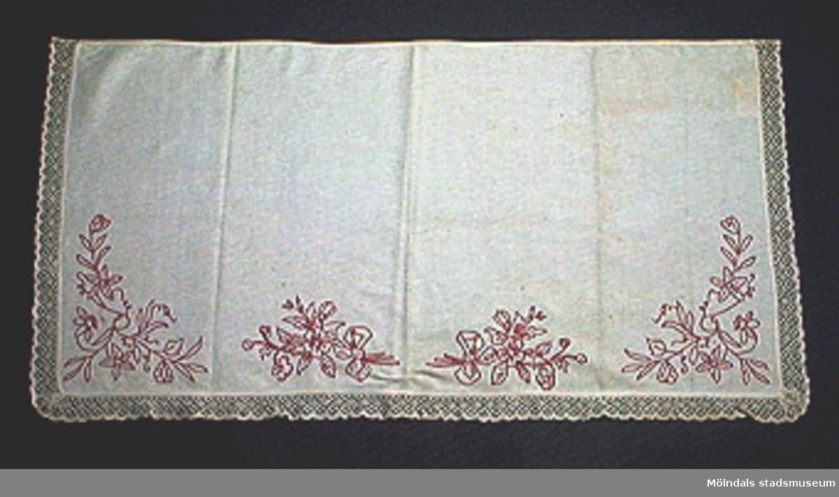 """Rektangulär vit duk med virkad spets i tre sidor. Röda stjälkstygnsbroderier i form av blomslingor.Ägaren/givaren är uppvuxen i Alegårdsslätt hos """"Stryk-Augustas"""". Hennes flicknamn var Johansson."""