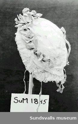 Dopmössa i tyll med sidenband. Se dopklänning SuM 1844.