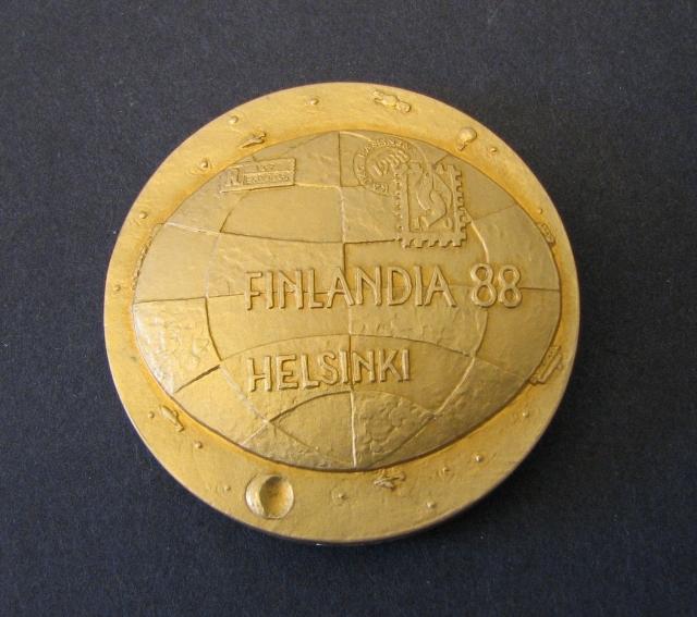 """Medalj i 925/1000 sterling silver och brons. Bestående av tredelar, två delar cirkulära och en rektangulär """"frimärksavgjutning""""vilken är placerad inuti de två. Åtsidan i sterling silver visar ettjordklot med frimärke, rek- etikett och stämpel samt texten""""FINLANDIA 88 HELSINKI"""". Frånsidan i brons visar en familj, man, kvinna, pojke och flicka i ett kuvert. Denrektangulära""""frimärksavgjut- ningen"""" i sterling silver visar Finlands förstafrimärke i valörerna 5 och 10 Kopek. Medaljen tilldelades Postmuseum för deltagande i utställningen."""