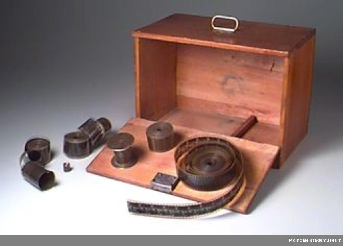 Svartmålad filmprojektor med filmrullar (5st) i en trälåda. Leksaksprojektor inköpt hos järnhandlare Karlsson. Julklapp till Nils 1923. Nils visade film för kamraterna för 1 öre eller en kola. Ficklampa sattes in baktill. Projektor och film förvaras i en brun trälåda med mässingshandtag upptill. De 5 filmrullarna på tema: hundar (1st), kameler och beduiner i öknen (2st), en pojke och en gammal man (1st) och landskapsvyer (1st).Lådan tillverkades av Nils far. Lådans storlek: L: 300 mm. B: 170 mm. H: 220 mm.