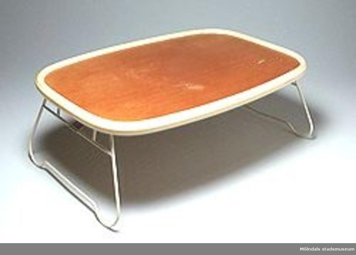 """Bricka med två infällbara stödben av plastad ståltråd. Brickan, i ljusbrunt trä, har rundade hörn och är kantad med plastsarg. Den är avsedd att användas för servering """"på sängen"""".Tidigare sakord: bricka, säng-.Tidigare specilabenämning: sängbord."""
