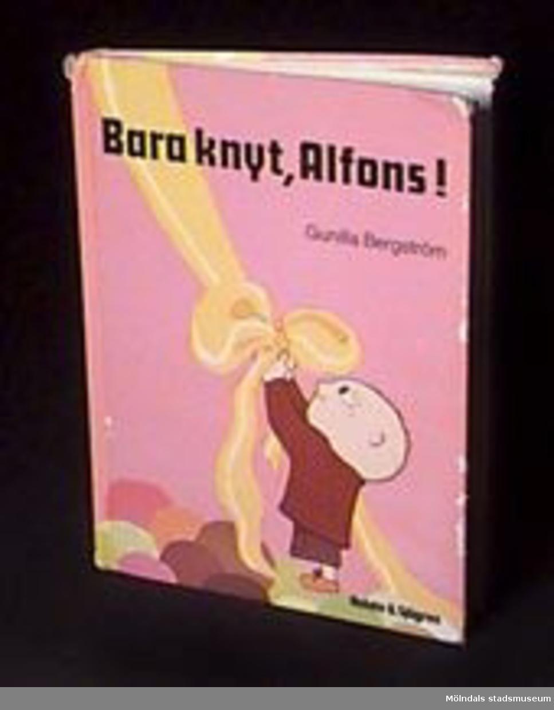"""Illustrerad sagobok för barn. Författare och illustratör: Gunilla Bergström. Titel: """"Bara knyt, Alfons!"""". Tryckt i Danmark 1988.Tidigare sakord: bok, barn-.Katrinebergs daghem var ett kollektivt daghem."""