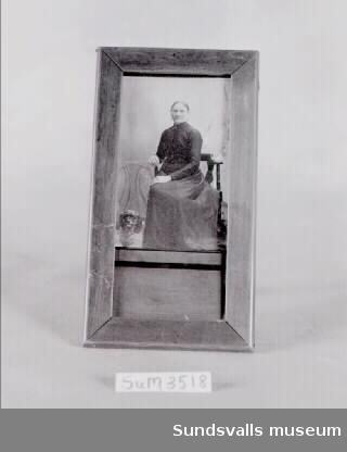 Fotografi i visitkortsformat i träram. Enligt anteckning ska fotografiet föreställa Märta Moberg sittande på en stol med en hund vid sina fötter.