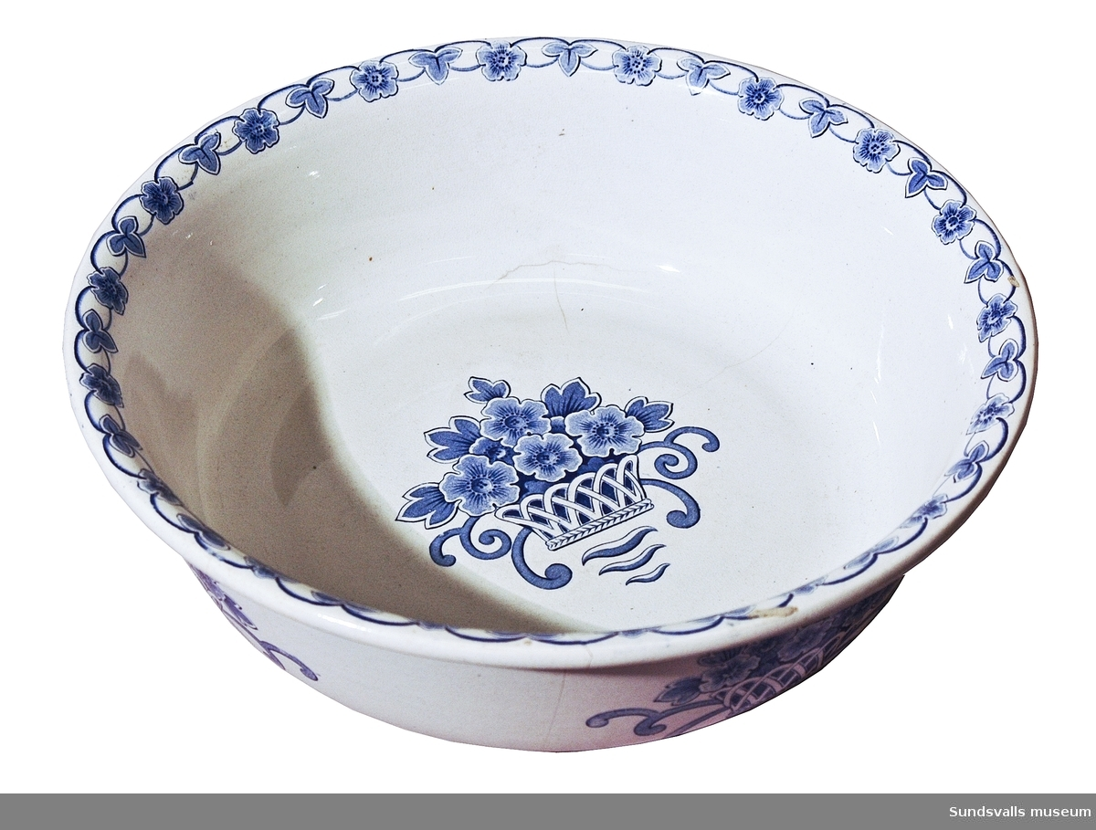 Tvättfat i porslin, använd på den år 1875 invigda 'Lindgrenska Arbetsinrättningen', sedemera pensionärshemmet Holmgården, Sundsvall. Tvättfatet är fabricerat på Rörstrands porslinsfabrik, mönster 'Korg', tillverkad 1920-1932, vit med mönster i blått i form av en blomsterkorg i botten och på sidorna. Blomranka runt brämen. Flintgods med handmålad dekor i blått. Mönsterformgivare Edward Hald. Litt.: Lagercrantz, Bo; Iris, Vineta och Grön Anna (Uddevalla 1986).