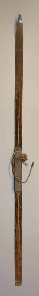 Skida av trä med hög rygg och låg spets. Undertill ränna med fyrkantig profil. Bindning med remmar av läder. Fotplatta förstärkt med räfflad gummi. Skidan med brun färg.