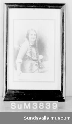 Fotografiskt porträtt inom passepartout, glas och ram. Vinröd, betsad träram. Porträttet föreställer Hildur Marit Hilda Rieck-Müller, född 21/12 1888, död 7/12 1913. Marit Rieck-Müller var dotter till Jacob och Maria Rieck-Müller. Fotografiet är signerat 'Ferd. Flodin 191' (den sista siffran saknas). Litt.: Maria Rieck-Müllers arkiv, Sundsvalls Kommunarkivs samlingar, Medelpads arkiv.