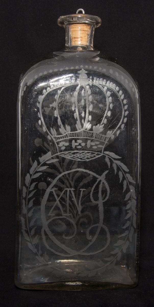 Brännvinsflaska av lätt gråtonad glasmassa, blåst i fyrkantig form, med graverad dekor: Carl XIV Johans monogram samt blomstergirlanger. Puntelmärke i botten. Glasmassan med orenheter och luftbubblor. Tillhörande kork förstärkt med en infattning med ögla av tenn.