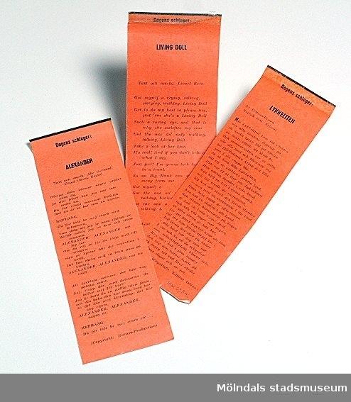 """Tre stycken schlagertexter urklippta ur tidningen Bildjournalen, en tidning för tonåringar. Texterna är följande: """"Lykkeliten"""", """"Alexander"""", """"Living Doll"""".Svart text tryckt på orange papper."""