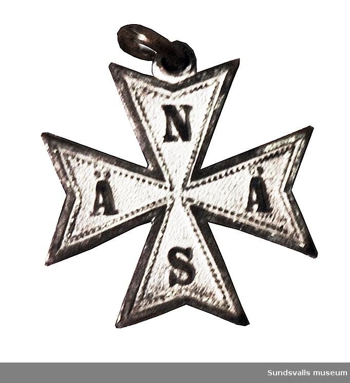 Berlock i metall i form av ett malteserkors med bokstäverna NÄÄS på vit botten.