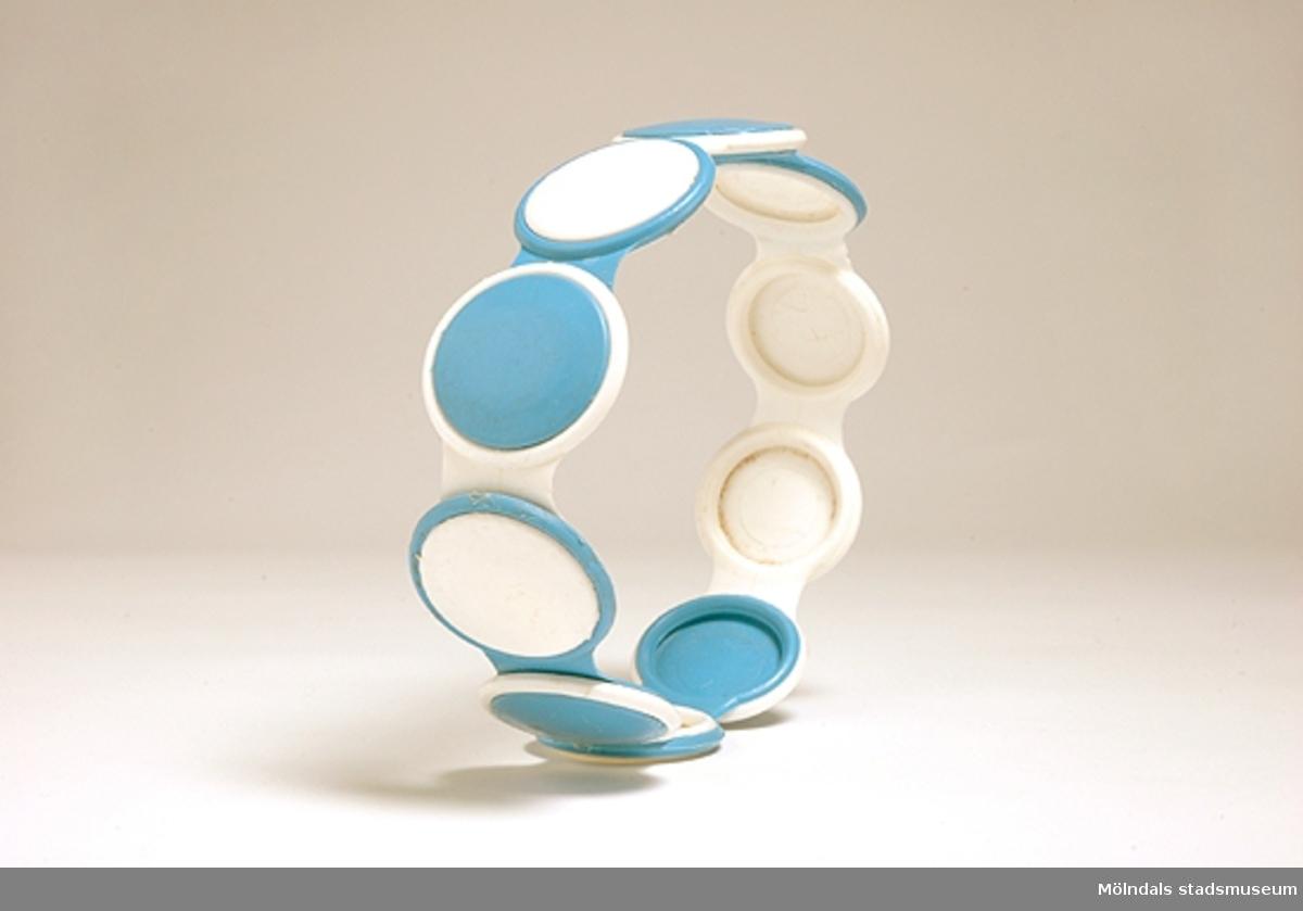 Ett plastskärp, ihopsatt av blå och vita plastdelar - ringar. Detta är bara en del av skärpet.Brukaren/givaren köpte dessa delar i Kållereds manufakturaffär och satte ihop skärpet i olika mönster. Plastringarna fanns i många olika färger och var mycket populära bland flickor i 8-10-årsåldern.