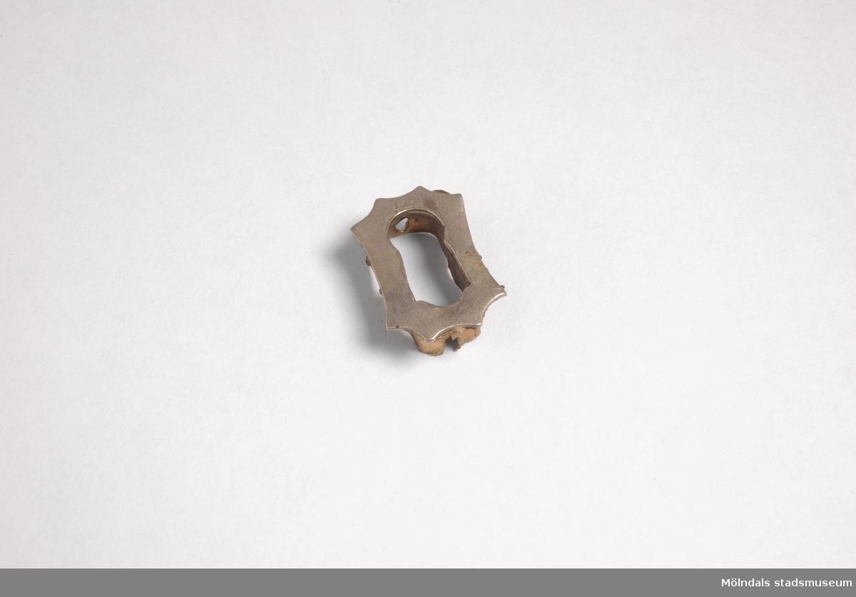 """Åttkantigt lådbeslag med nyckelhål.Redskap och verktyg kommer från Lindströms snickeri (Gamla Riksvägen 81, Ekebacken). Här byggde John Lindström från Lindome ett boningshus och snickeriverkstad 1928. Han öppnade ett snickeri som specialiserade sig på köksbord Borden levererades till en grossist i Göteborg. Som mest tillverkades 50-60 bord i veckan. Borden hade ben av björk och resten var av furu. Han gjorde även andra möbler på beställning. Till hjälp hade John ett par anställda.De sista åren gjordes mest renoveringar och reparationer, medan det """"begav sig"""" de mest aktiva åren tillverkades bord av alla de slag."""