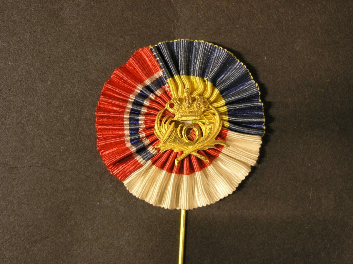 Nålmärke i metall med krönt postemblem med kvistar. Emblemetomgivet av kokard i textil i de tre nordiska ländernas färger,Danmark, Sverige och Finland. Veckad.