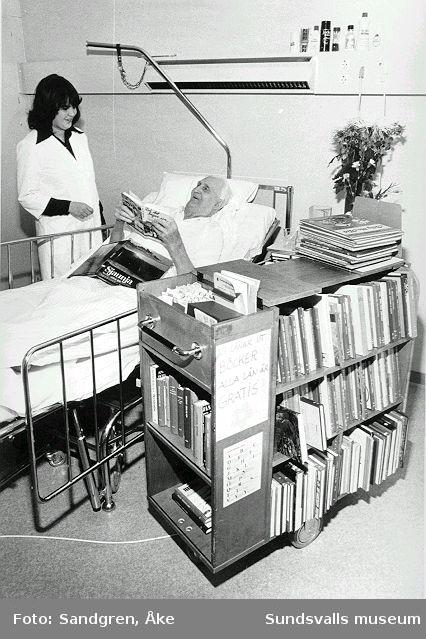Elisabeth Månsson med bokvagn besöker patient på sjukhussal.