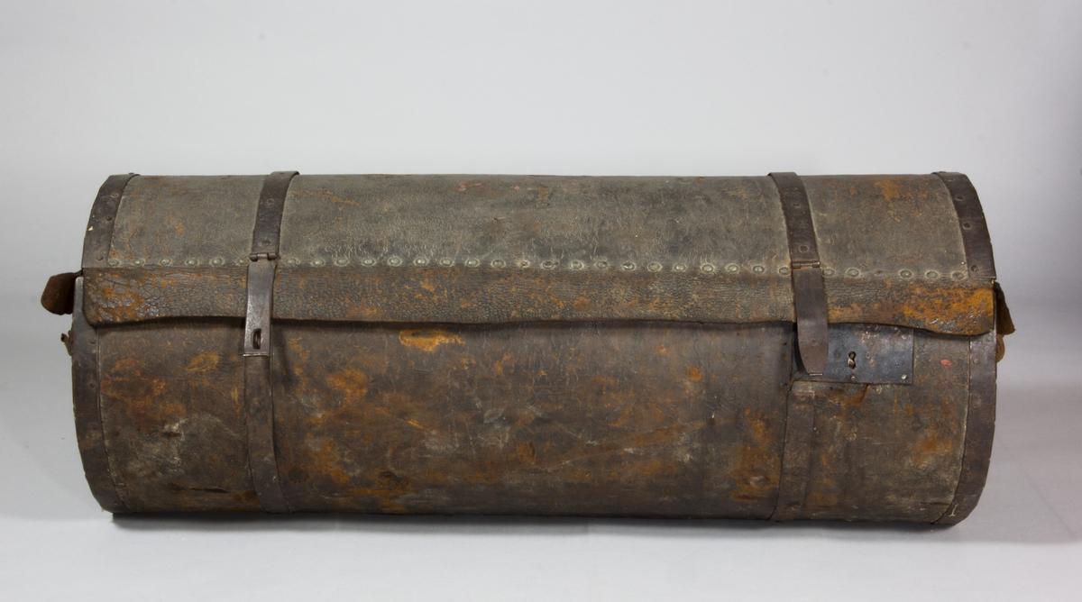Koffert, cylindrisk till formen. Stomme i trä, överklädd med skinn. Ändarnas kanter klädda med metall. Kan tillslutas med hjälp av två metallband som löper runt kofferten mitt på. Insidan klädd med ljust papper. Handtag på ändarna.