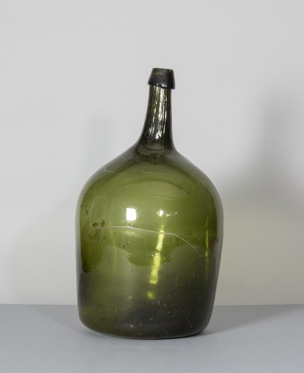 Flaska i grönt glas. Rundade sidor, hals med halsring, flat botten. Eventuellt använd för förvaring av ättika.