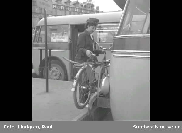 Busstationen i Sundsvall. Kvinnlig busschauför hänger upp en cykel på fronten på bussen, man pekar på en karta.