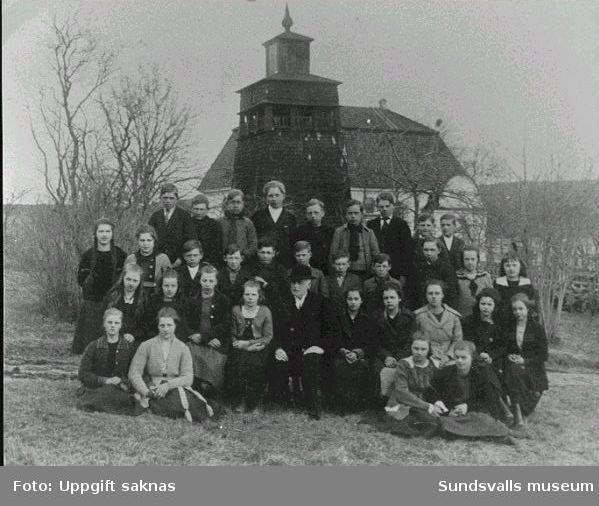 Konfirmationsgrupp utanför Attmars kyrka troligen 1920-tal. Prästen Per Bill och konfirmanden Ingeborg Muhr, andra flickan t h om prästen.