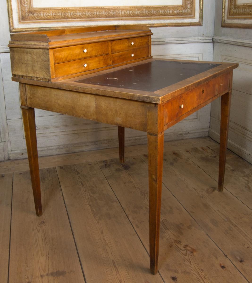 Skrivbord med uppsats av brunbetsad björkfaner på furu. Med infälld mörk vaxduk och med låda på kortsidan med nyckelhålsbussning av mässing och två knoppar av ben. Raka nedåt avsmalnande ben. Uppsatsen med trågsarg och fyra draglådor med knoppar av ben. Den högra nedre lådan med fackinredning för skrivsaker.
