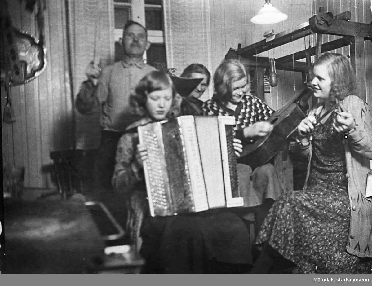 """Familjen Hansson spelar och sjunger i köket år 1932. Hjalmar Hansson (1880-1970) arbetade på Papyrus.  """"Familjen Hansson är samlad i farmors kök på Nybyggaregatan 21 på Kikås. Här är min söta och snälla Mamma Karin som försöker spela dragspel. Hon kunde inte utan bara poserade. Min älskade mor föddes 1913 och dog 1992. Farfar Hjalmar försöker vara dirigent. Min rekorderliga farmor Berta skymtar tyvärr bara bakom. Min faster Märta knäpper på en gitarr och faster Brita spelar på något instrument eller bara låtsas. Det är svårt att se.""""  (Berättat av Hans Hansson)"""