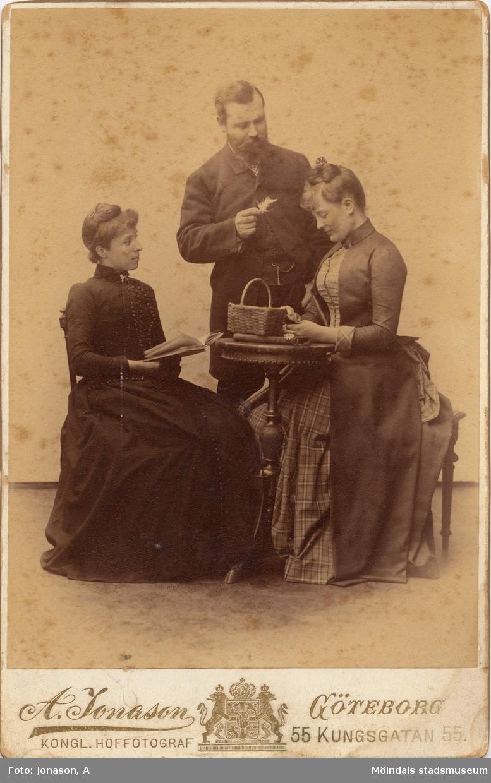 Ateljébild, två damer sittande vid bord, en herre står bakom med en fjäder i handen. Mannen är Martin Stenström som ägde godset Kristinedal och firman Buhrmans änka, damkollektion. Kvinnan till höger är Kerstin Stenström född Svanfeldt, kvinnan till vänster är okänd.
