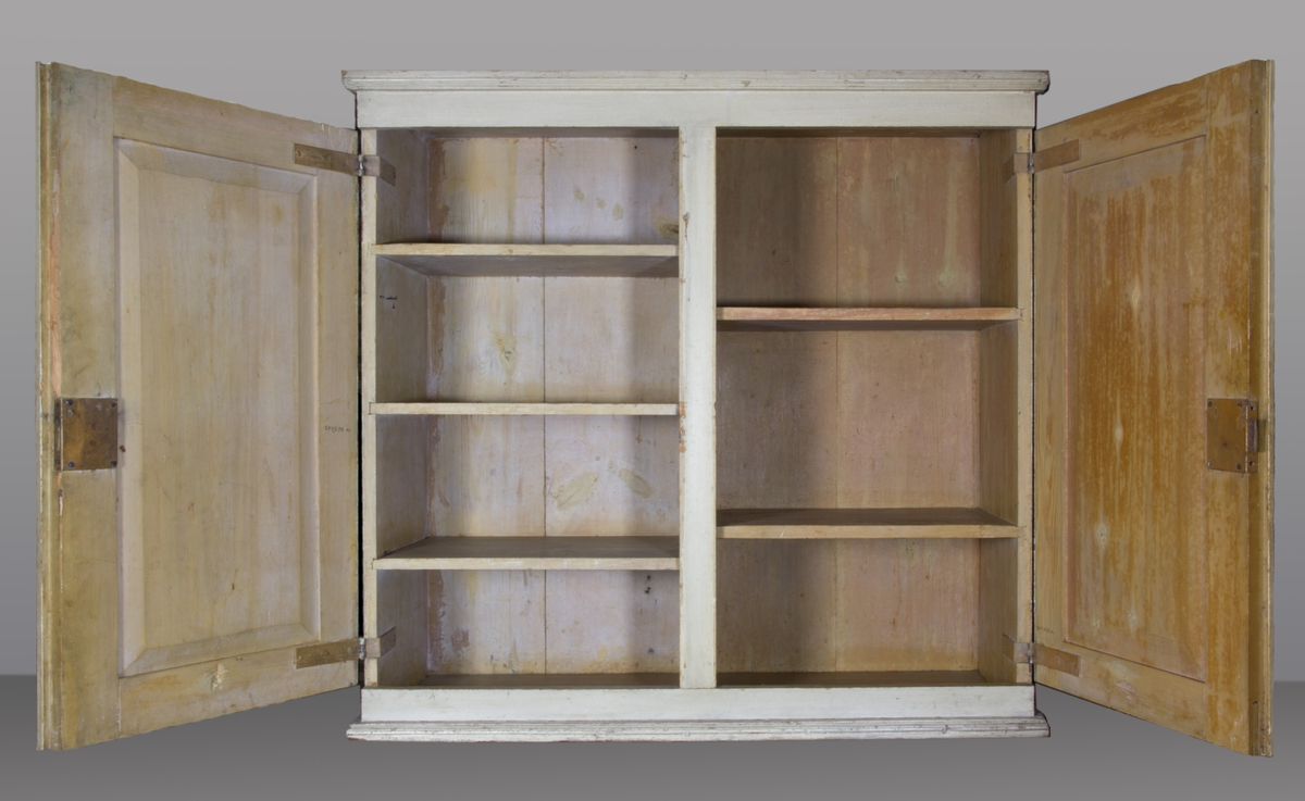 Medicinskåp, sannolikt furu. Vitmålat. Dubbla spegeldörrar med separata lås. Inuti skåpet fyra hyllplan till vänster, tre till höger.