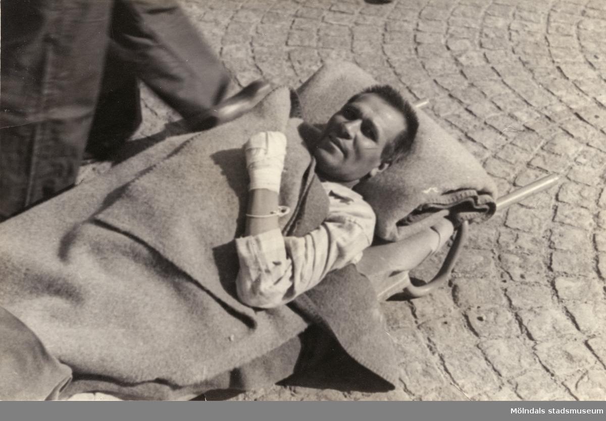 """""""Karantänsförläggning"""" på Kvarnbyskolan för flyktingar från koncentrationsläger i Tyskland 1945. En manlig flykting på bår, buren av Röda Korsets personal."""