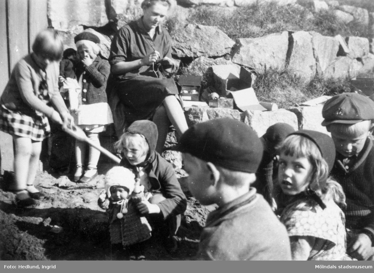 Bosgårdens barnträdgård 1938-1945. Förskollärare och barn som leker utomhus.