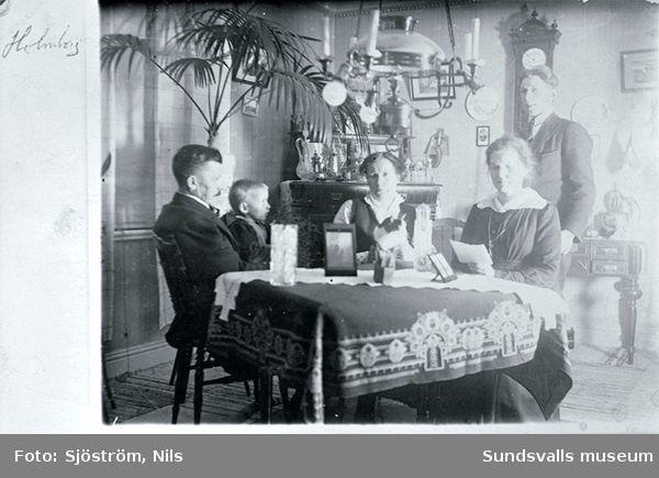 heminteriör. Familjen Holmberg, fadern Johan, modern Tilda samt sönerna Hilding och Fridolf (t v) samt en okänd kvinna.