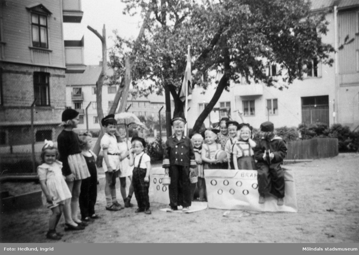 Troligtvis daghem i Guldheden, Göteborg 1945-. Flera barn som står på en lekplats.