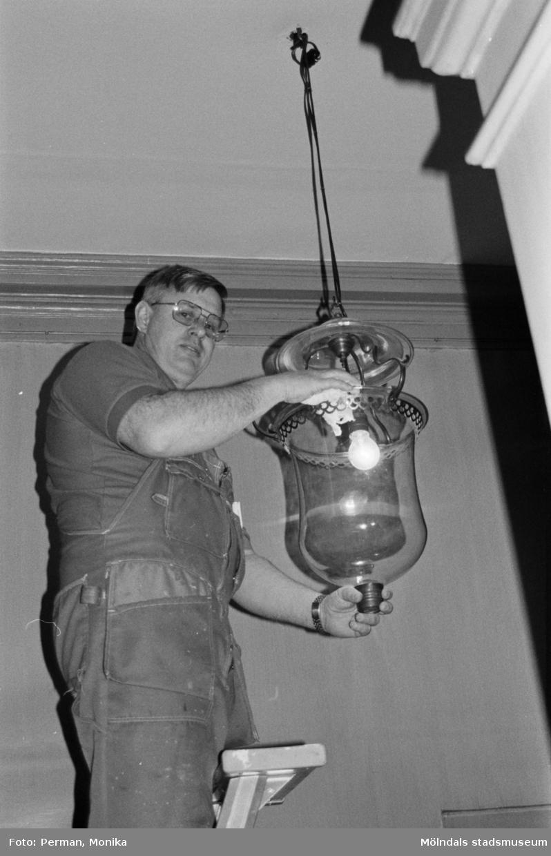 Antikvarisk storstädning på Gunnebo slott 1992. Tekniker Alf Garthman står på en stege och håller en taklampa i händerna.