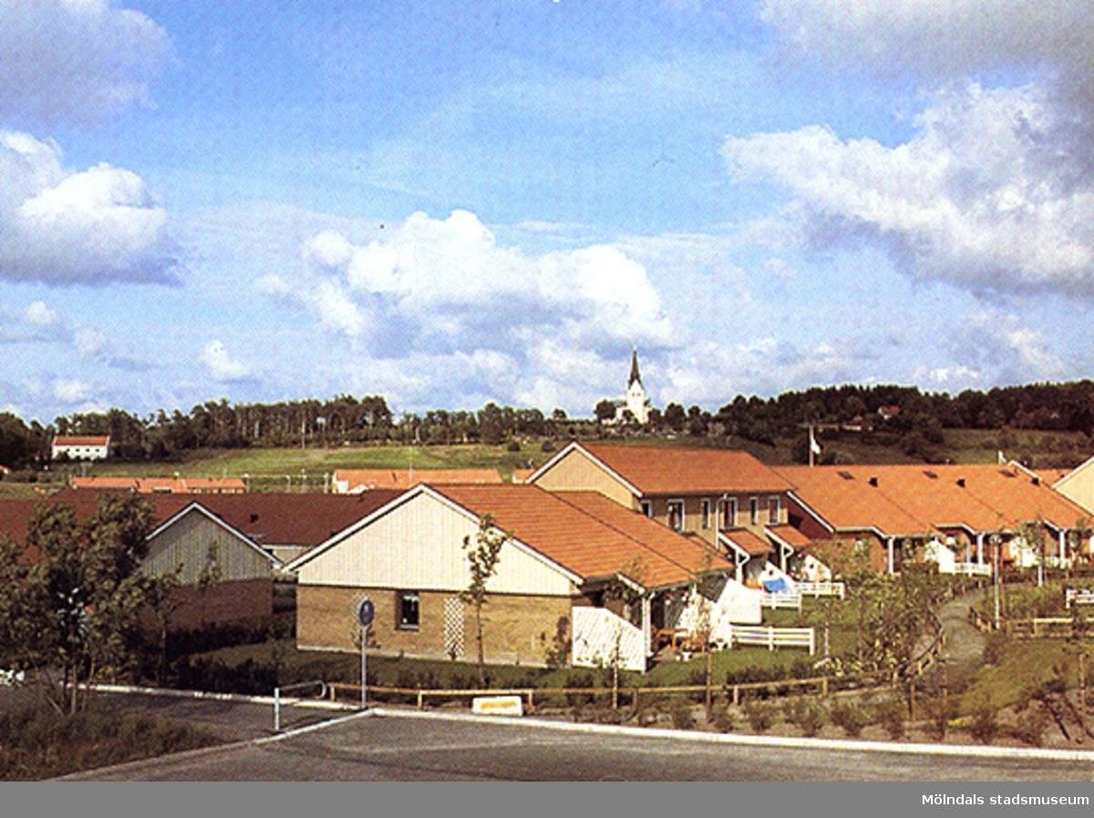 Vykort på bostadshus i Kyrkängen. Lindome kyrka syns i bakgrunden.