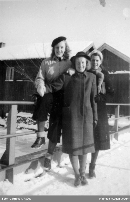 Astrid Karlssons (gift Garthman) kompisar sitter/står vid en bro i ett vinterklätt Kvarnbyn. Karin Karlsson står i mitten, de två andra är okända för givaren. 1930-tal.
